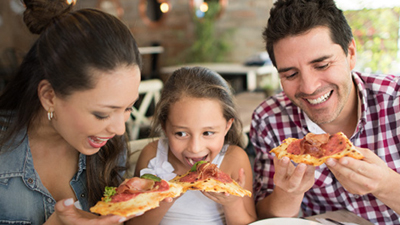Woman, child and man sitting next to each other about to to eat slices of pizza